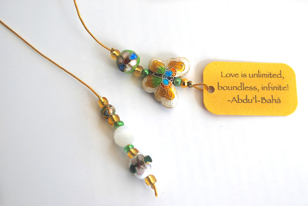 White and pistachio green cloisonne beaded bookmark with quote 'Love is unlimited...'