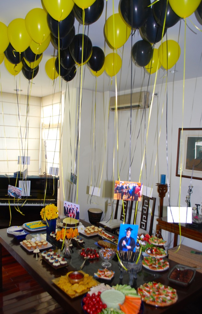 The dining table covered in treats for the graduates and their photos hanging from helium balloons